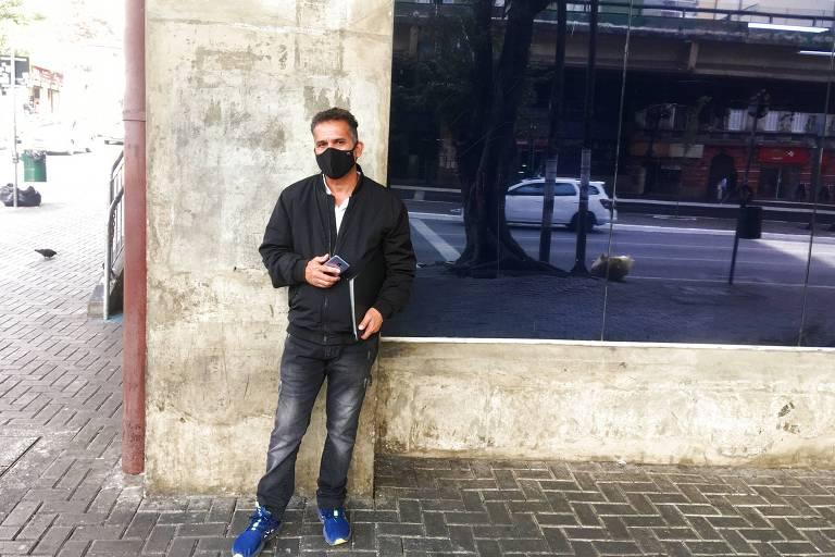 O ex-vigia Sérgio Batista Silva, desempregado há dois meses ao lado de uma parede espelhada, com uma pasta e um celular nas mãos