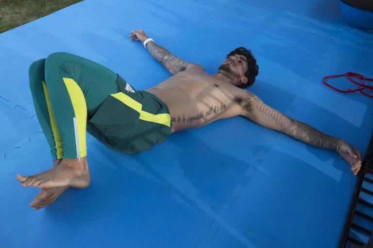 Medina deitado e se esticando num tapete azul, com calça verde e amarela