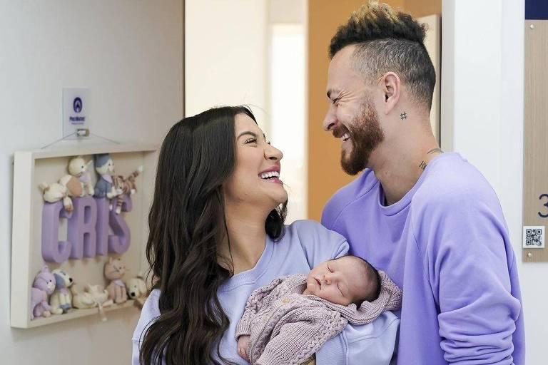 Casal branco de cabelo preto segurando bebê, todos usam roupas com tonalidades de roxo e lilás