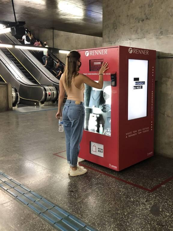 mulher em frente a uma vending machine no metrô