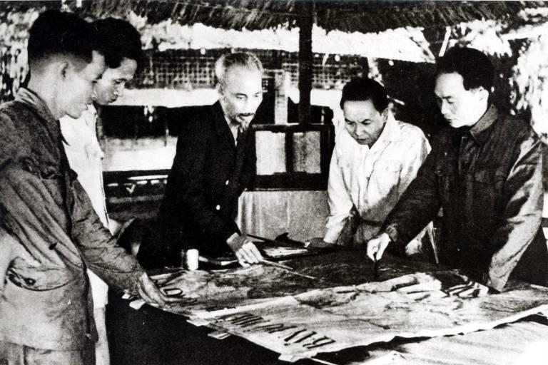 Na imagem, é possível ver Ho Chi Mihn apontando para posições em um mapa aberto sobre a mesa enquanto conversa com quatro pessoas que o observam dentro de um acampamento militar