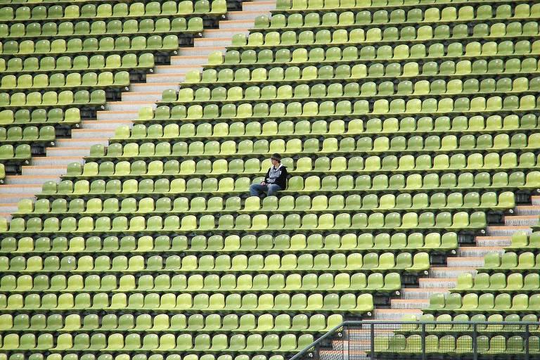 Homem sozinho na arquibancada de um estádio