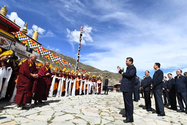 Imagem mostra o presidente chinês Xi Jinping e outros homens com terno, ao lado esquerdo da foto, conversando com monges, localizados no lado direito da imagem
