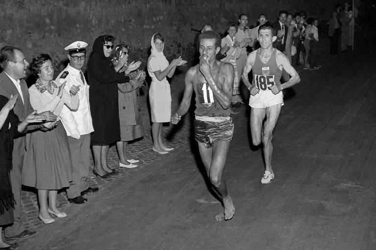 O etíope Abebe Bikila corre descalço durante maratona nos Jogos Olímpicos de Roma, em 1960; corredor não gostou dos tênis oferecidos pela patrocinadora e acabou ganhando a prova e batendo recorde mundial