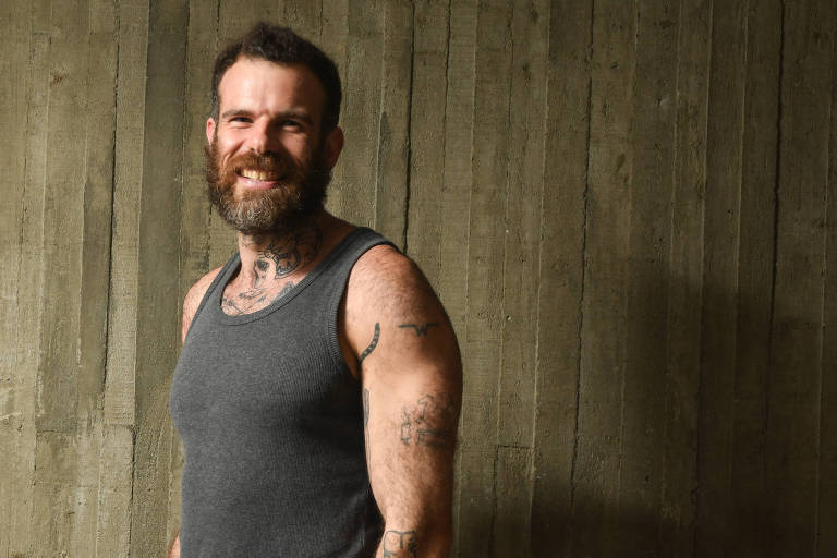 Chico Felitti, de camiseta regata cinza, sorri para foto