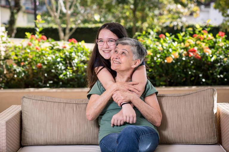 Elda, de 78 anos, e sua neta Letícia, de 11, se abraçam num sofá.