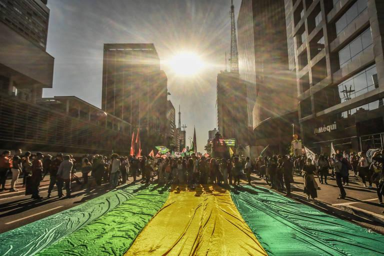 Foto mostra bandeira estendida na avenida Paulista durante atos contra o governo de Jair Bolsonaro neste sábado