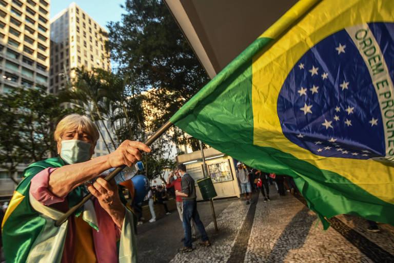 """Foto mostra  Ana Maria Rodrigues, 74, diretora da CMB (Confederação das Mulheres do Brasil), com a bandeira brasileira nas costas; ela contou que a aposta no uso da peça com o emblema da nação tem o propósito de reunir """"uma ampla frente para derrotar Bolsonaro"""""""
