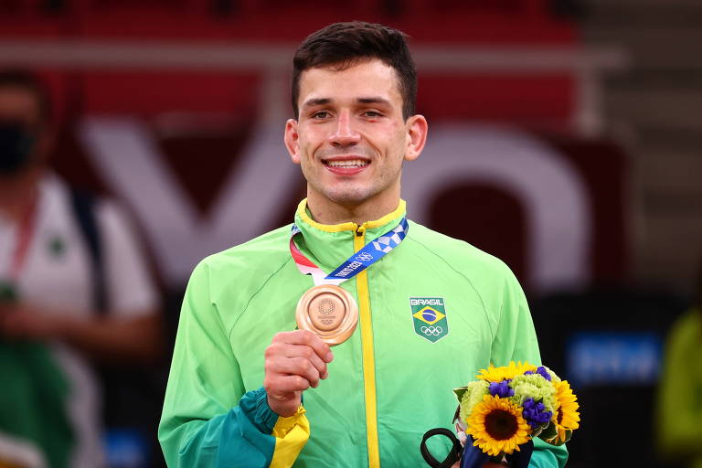 O judoca brasileiro Daniel Cargnin com sua medalha de bronze, conquistada neste domingo (25)
