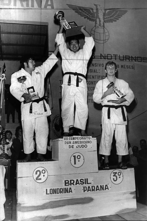 Chiaki Ishii segura o troféu de campeão do Pan de judô de 1970; abaixo do pódio estão Roy Yamamoto (EUA) e Gordon Gregory (Canadá)