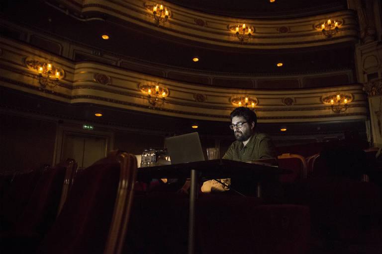 Homem branco mexendo no computador num teatro