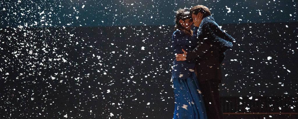 Homem e mulher se beijam sob neve em palco