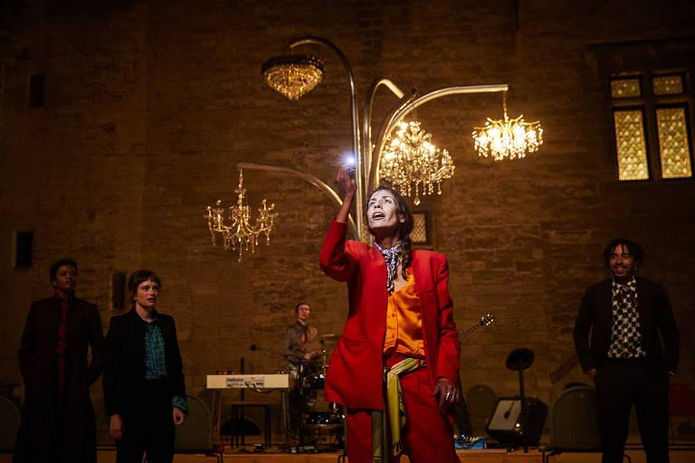 Homem olha lustre grande ao lado de pessoas em palco, decorado como ferroviária
