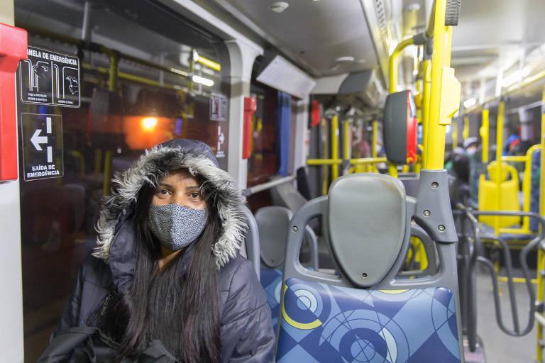 Mulher branca com uma blusa cinza, de capuz, cabelo preto longo, de máscara cinza escuro, sentada dentro de um ônibus com poltronas azuis e barras de apoio amarelas