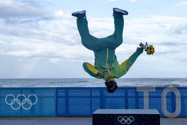 Italo está no ar, de ponta-cabeça, dando uma pirueta em cima do pódio, com o mar ao fundo