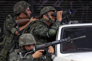 Army soldiers take position during an operation at Morro do Alemao slum in Rio de Janeiro