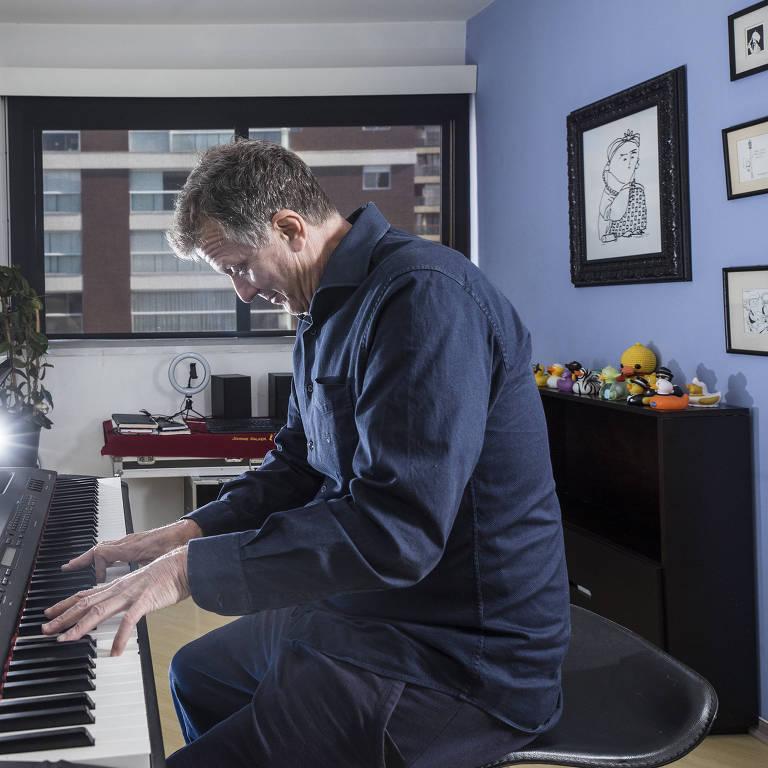 homem branco toca um teclado em sua sala de estar