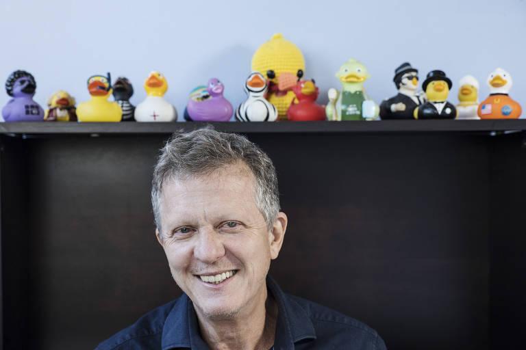 homem branco de cabelos grisalhos está sentado na frente de uma prateleira cheia de estatuetas de patos coloridos