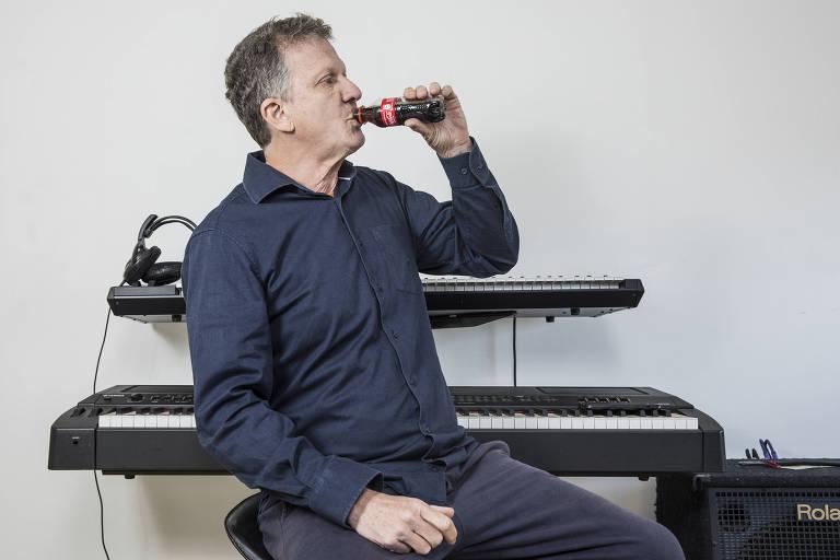 homem está sentado em banqueta e toma coca-cola