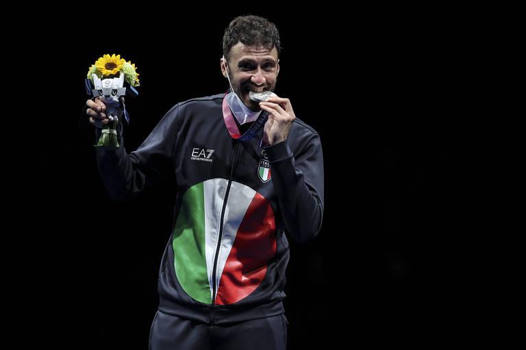 O esgrimista italiano Luigi Samele morde medalha de prata que conquistou nos Jogos de Tóquio