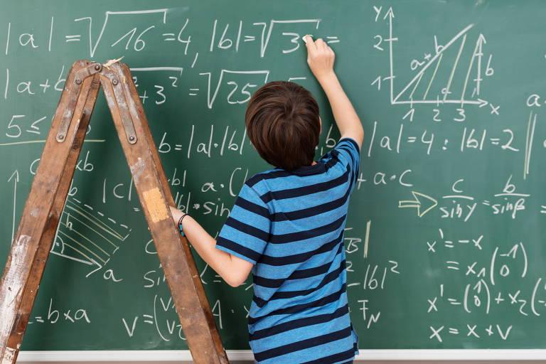 Lousa verde com números, cálculos e gráficos desenhados em giz branco e um menino de costas usando uma camiseta listrada de azul e preto escrevendo, com a mão apoiada em uma escada de madeira