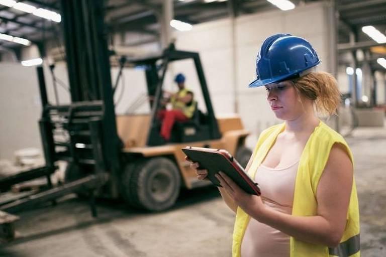 Mulher grávida de colete e capacete em um galpão, com uma empilhadeira ao fundo