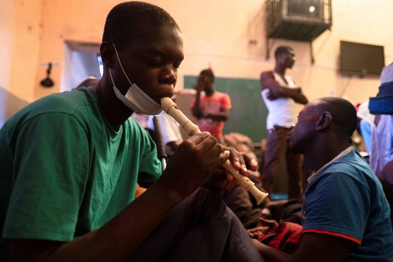 Foto mostra rapaz negro tocando flauta doce em uma escola, há pessoas atrás dele