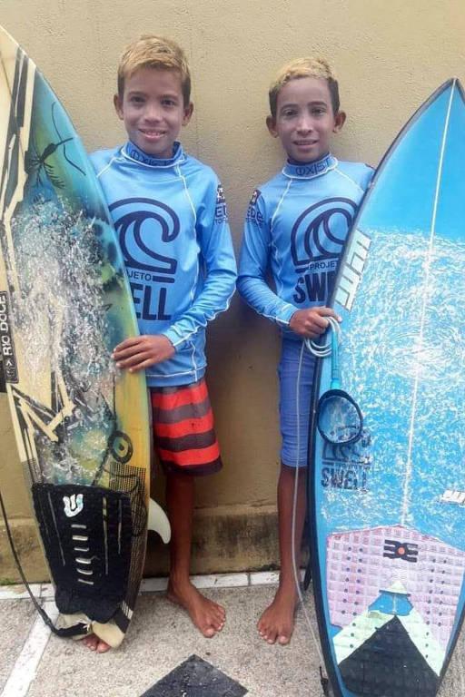 dois irmãos com roupa de surfista e pranchas