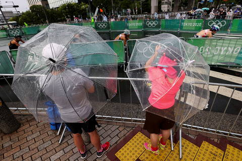 Tokyo 2020 Olympics - Triathlon - Women's Olympic Distance - Final - Odaiba Marine Park, Tokyo, Japan July 27, 2021. Fans and residents try to catch a glimpse of the women's triathlon event in the rain caused by tropical storm Nepartak.  REUTERS/Issei Kato ORG XMIT: GGGTOK602