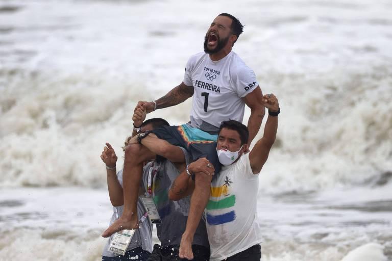 O surfista Ítalo Ferreira é carregado nos ombros por companheiros após ganhar a medalha de ouro