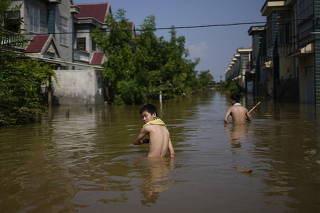 Children wade through floodwaters following heavy rainfall at a village in Xinxiang