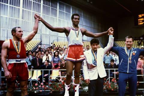 O campeão cubano Teofilo Stevenson (ao centro, medalha de ouro), o soviético Pyotr Zaev (à esq., medalha de prata) e o alemão Jurgen Fanhanel (à dir., melhada de bronze) no pódio no prêmio de Boxe Peso Pesado, em Moscou (Rússia). *** Cuban champion Teofilo Stevenson (C-gold medal) Soviet Pyotr Zaev (L-silver medal) and German Republic Democratic Jurgen Fanghanel (R- bronze medal) wawe on the podium of the Olympic heavyweight 81+ boxing event that won Teofilo Stevenson. Stevenson --who won 301 of the 321 fights he took part-- died of a heart attack at the age of 60 in Havana on June 11, 2012. AFP PHOTO ORG XMIT: AGEN1206112149399892