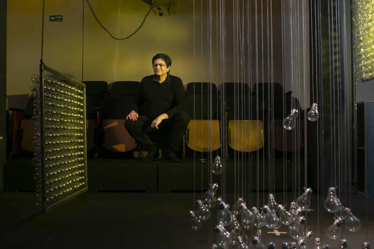 Homem, vestido todo de preto, sentado em uma cadeira de teatro. Na frente dele, uma arte feita com várias lâmpadas