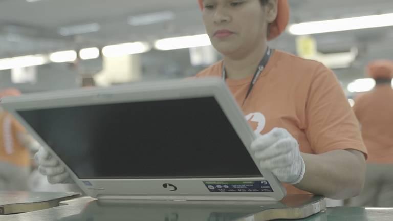 Operária segura a tela de um notebook
