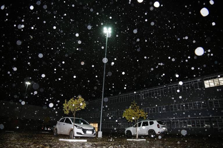 Imagem mostra dois carros na rua e neve caindo do céu