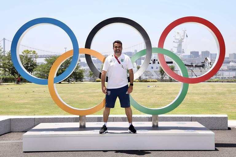 Homem em frente a aros olímpicos
