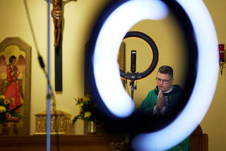 Ring lights are used to illuminate Father Bryan Small as mass is live streamed at Saints Peter and Paul Catholic Church in Atlanta