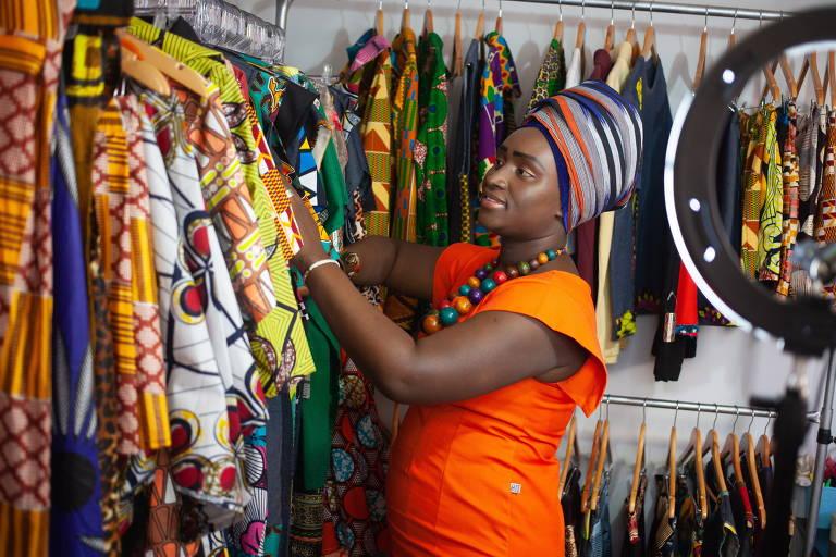 Estilista Saturnina da Costa, natural de Guiné-Bissau, usa turbante e vestido da sua marca, com referências africanas. Ela está organizando um mostruário com peças de sua coleção
