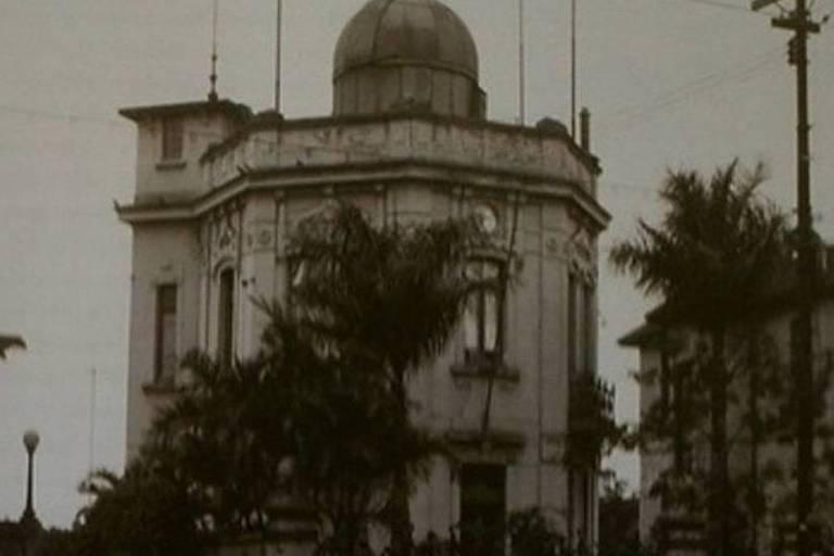 Fotografia antiga mostra fachada de um prédio em meio a árvores
