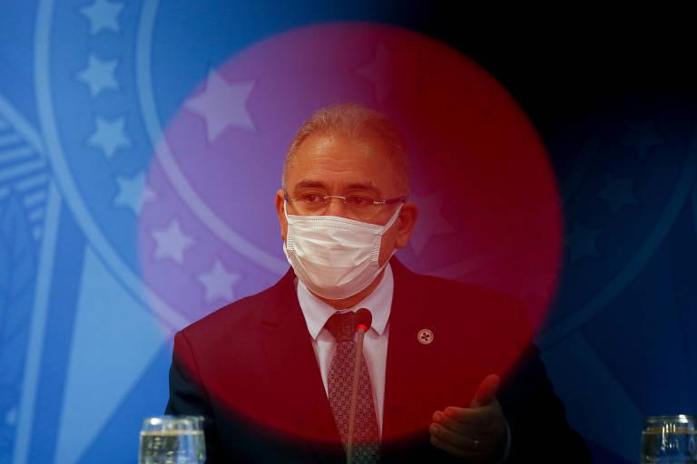 Queiroga, usando terno e máscara, diante de um fundo azul. Um círculo de luz vermelha está sobre o rosto do ministro