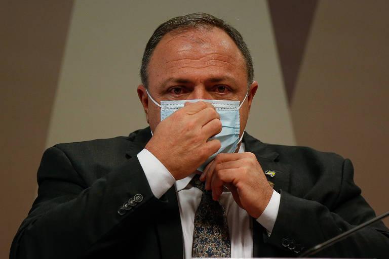 Homem ajeita com a mão direita uma máscara de cor azul