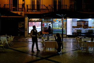 A waiter wearing a face mask talks with a woman as she eats on an empty terrace of a restaurant at Augusta street in Lisbon