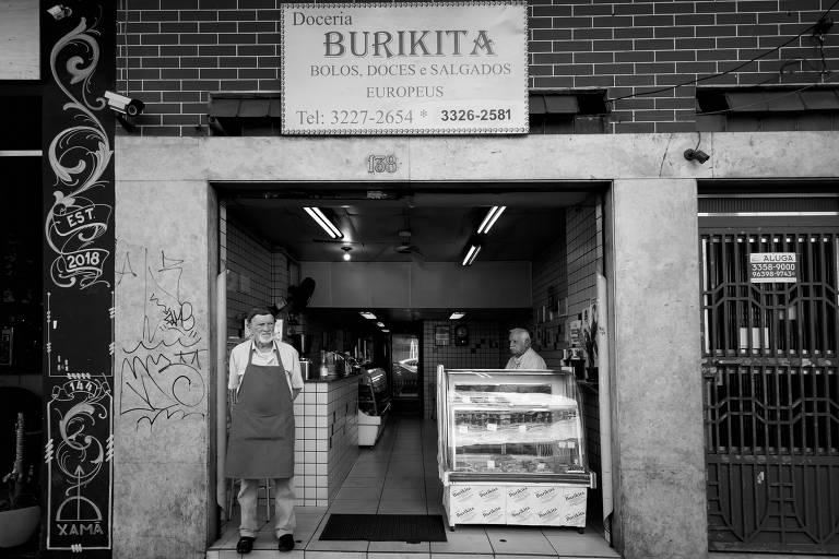 Homem idoso veste avental em frente a estabelecimento comercial; no topo, se lê o nome do lugar: Burikita