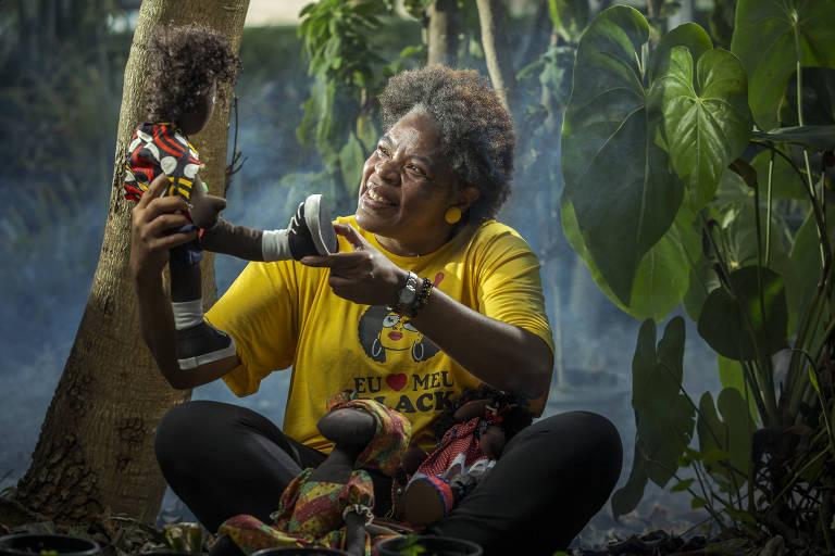 A professora Gilda é uma mulher negra, com cabelo black power castanho; ela veste uma camiseta amarela, uma calça preta, usa brincos amarelos e está sentada com as pernas cruzadas, com plantas ao fundo; ela segura uma boneca de pano negra nas mãos, para a qual olha enquanto sorri, e está com outras bonecas de pano negras no colo