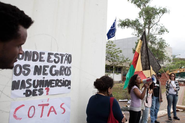 Estudantes carregam bandeiras e um megafone  na reitoria da USP; Na parede, um cartaz diz: Onde estão os estudantes negros nas universidades? Cotas