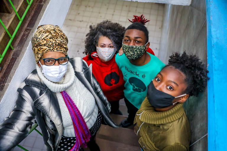 A foto mostra quatro pessoas negras, integrantes do projeto Afroativos, lado a lado, abraçadas e de máscara; Maiza Lemos, a primeira, está de casaco e turbante, seguida pela professora Larisse Moraes, que veste um agasalho vermelho, e os estudantes Alisson e Ketllyn