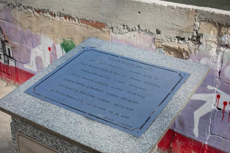 """Memorial construído em homenagem aos meninos mortos. Placa de metal sobre pedra de granito com o dizer """"Nossos mortos têm voz"""". Abaixo da frase, os nomes dos meninos e a data de cada assassinato."""