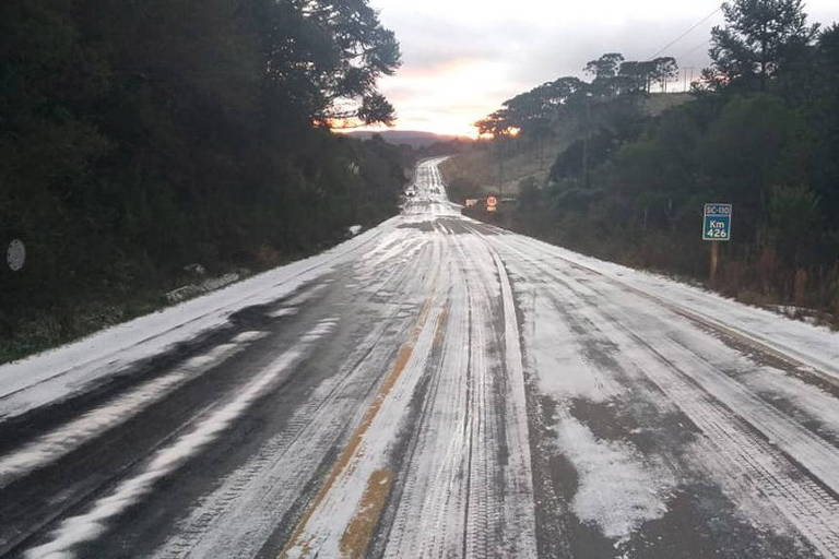 Imagem mostra rodovia vazia, com partes brancas de sal e gelo no asfalto