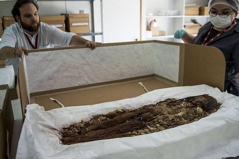 Um homem, sem máscara, e uma mulher, com máscara, observam uma múmia disposta sobre uma mesa