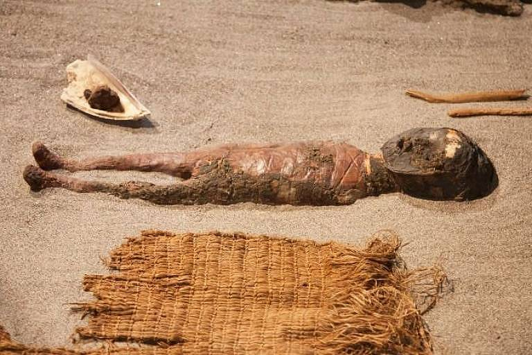 Múmia aparentemente de uma criança está disposta sobre uma superfície